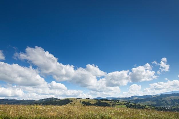 Prado, montanha e céu azul com nuvens