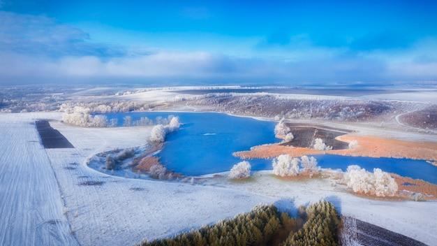 Prado nevado com tiras da floresta e campos agrários vazios. paisagem de inverno.
