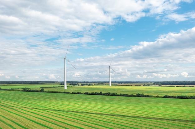 Prado verde com turbinas eólicas gerando eletricidade, paisagem de verão com céu azul, fontes de energia alternativas