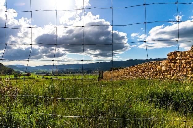 Prado verde em um dia com nuvens brancas e cinzentas e raios de sol com montanhas ao fundo atrás de uma cerca.