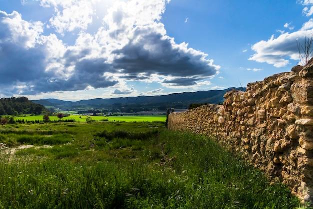 Prado verde em um dia com nuvens brancas e cinzentas e raios de sol com montanhas ao fundo.