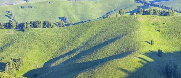 Prados verdes e encostas de montanhas, luz da manhã