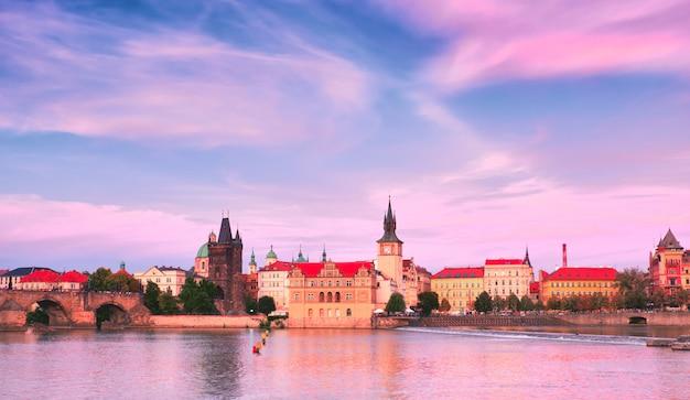 Praga, beira-rio no pôr do sol, com charles bridge no horizonte direito e histórico em frente