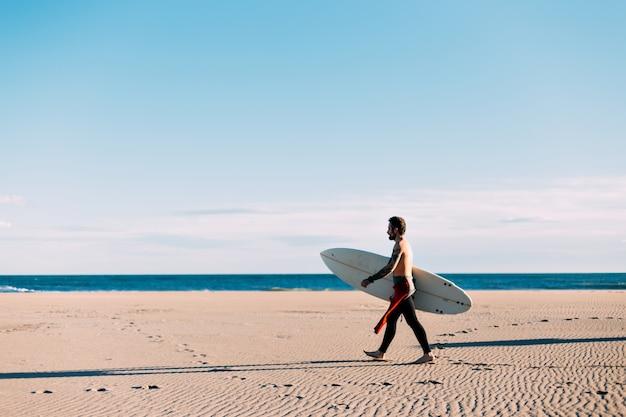 Praia aberta e vazia com surfista solitário em traje de mergulho, caminhar em direção à costa do mar ou oceano com prancha de surf