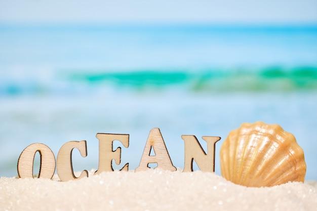 Praia abstrata - areia e mar como pano de fundo com o oceano e a concha do mar de inscrição. conceito de viagens de lazer.