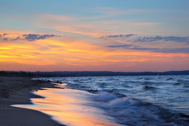 Praia ao pôr do sol com nuvens