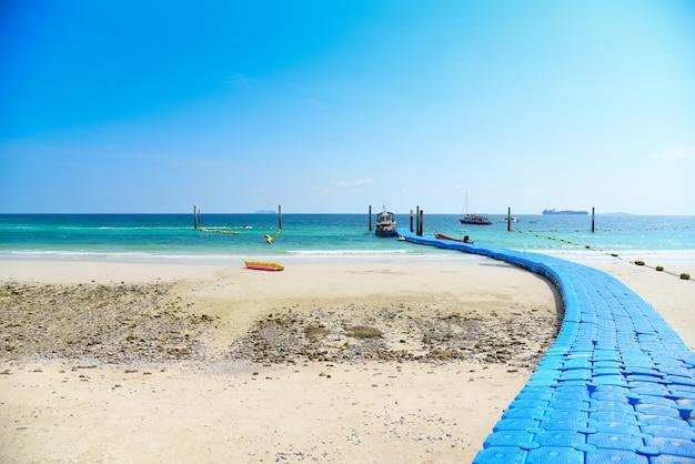 Praia areia tropical verão ilha azul água com céu brilhante e pontão de plástico mar flutuante ponte