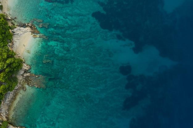 Praia azul com montanhas rochosas e águas cristalinas do mar adriático em dia ensolarado vista aérea do drone