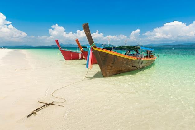 Praia branca da areia e barco da longo-cauda na ilha de khang khao (ilha do bastão), a província bonita de ranong do mar, tailândia.