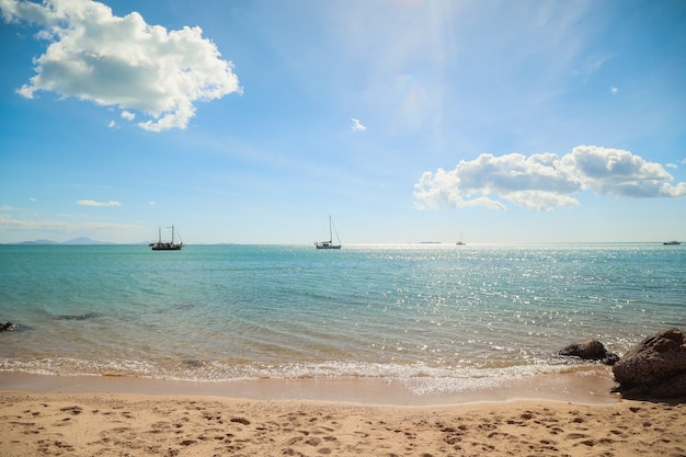 Praia cercada pelo mar com navios e colinas sob o sol