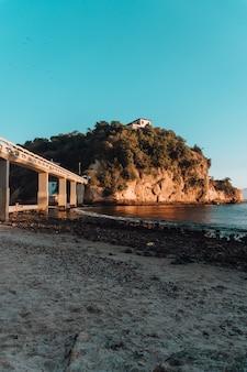 Praia cercada pelo mar e pedras cobertas de verde com uma ponte no brasil