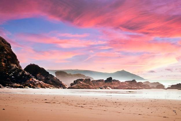 Praia cercada por pedras e mar sob um céu nublado durante um lindo pôr do sol rosa