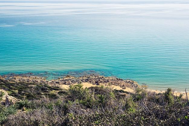 Praia coberta de mato do mar mediterrâneo no norte de chipre