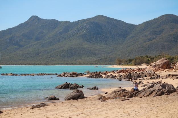 Praia coberta de pedras cercada pelo mar e morros cobertos de florestas sob o sol