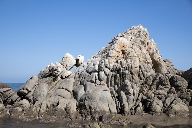Praia coberta de pedras cercada pelo mar sob o sol e um céu azul no méxico