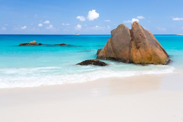 Praia com água azul e céu azul e areia branca e algumas rochas