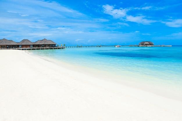 Praia com bangalôs aquáticos nas maldivas