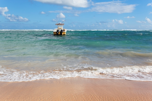 Praia com barco no mar e céu azul