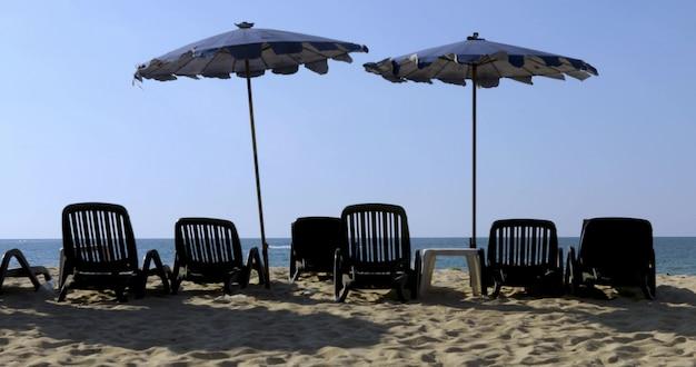 Praia com espreguiçadeiras guarda-sóis