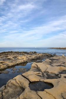 Praia com grandes pedras e mar calmo