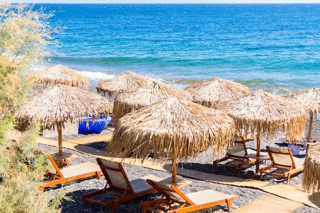 Praia com guarda-sóis e espreguiçadeiras à beira-mar em santorini