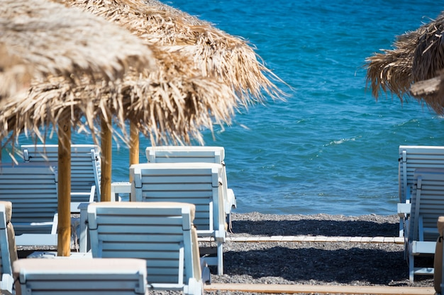 Praia com guarda-sóis e espreguiçadeiras em santorini