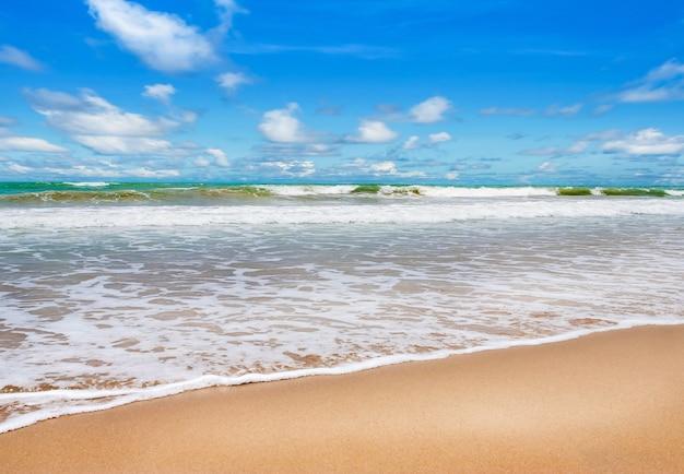 Praia com mar azul e areia branca no céu azul