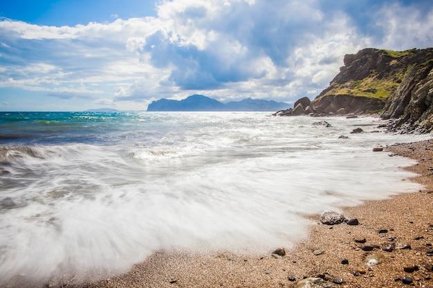 Praia com montanhas no fundo. as montanhas são cobertas de grama e tem penhascos íngremes do mar. céu está nublado