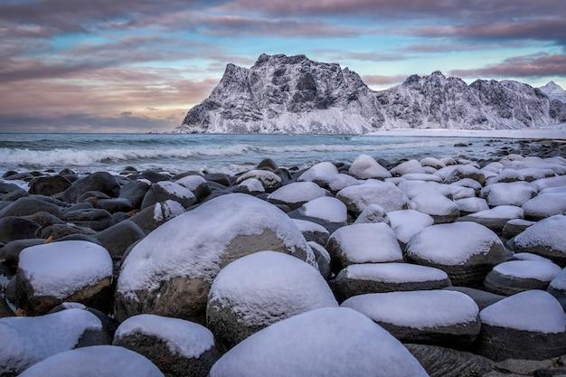 Praia com pedras cobertas de neve e montanhas ao fundo nas ilhas lofoten, noruega