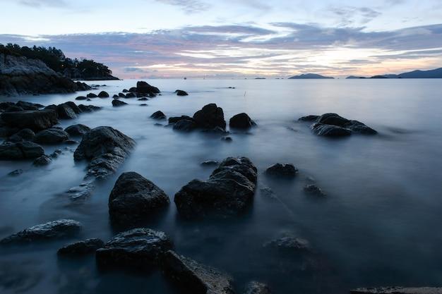 Praia com pedras e ondas; fundo do sol