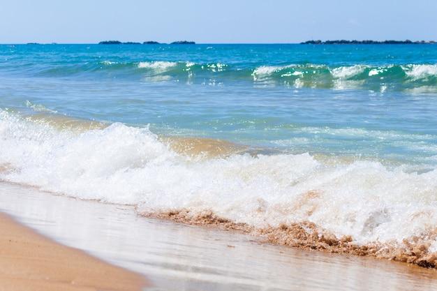 Praia da areia, ondas do mar e céu azul. turquia, mar mediterrâneo.