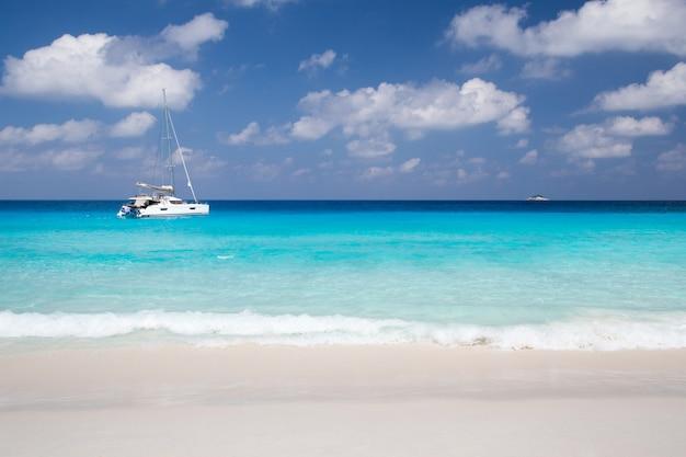 Praia de areia branca com águas turquesa e pedras