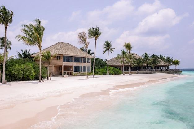 Praia de areia branca com edifícios de madeira