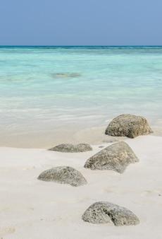 Praia de areia branca com pedra