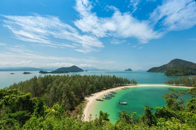 Praia de areia branca e barco de cauda longa na ilha kham-tok (koh-kam-tok)