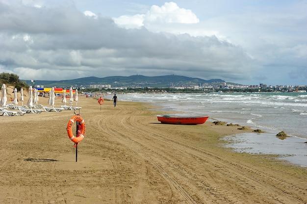 Praia de areia com barco e uma tábua de salvação em anapa