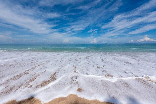Praia de areia com bolhas de ondas, mar azul e céu