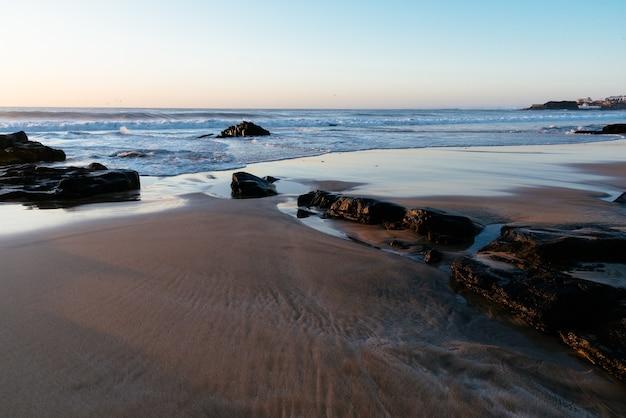 Praia de areia com céu azul claro durante o dia