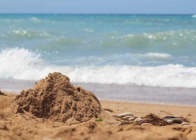 Praia de areia contra o céu azul e as ondas do mar, antes da tempestade que se aproxima. detalhe de água e areia.