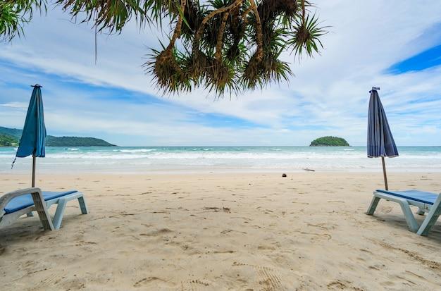 Praia de areia de verão com cadeira de praia e ondas de espuma do mar colidindo com a água turquesa do oceano e céu azul nuvens brancas sobre o mar fundo natural para férias de verão site de viagens