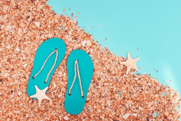 Praia de areia e chinelos e verão com pequenas estrelas do mar