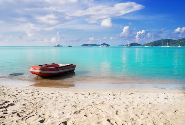 Praia de areia e mar azul com barco no céu azul