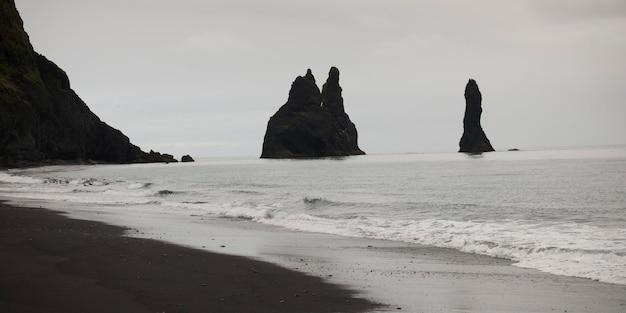 Praia de areia, falésias escarpadas no oceano