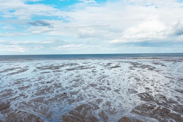 Praia de areia, mar e céu azul nublado na inglaterra em dia ensolarado