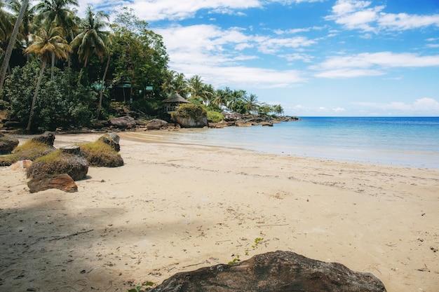 Praia de areia no mar com o céu azul.