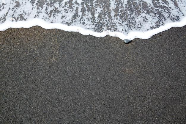 Praia de areia preta com espuma de ondas fuerteventura