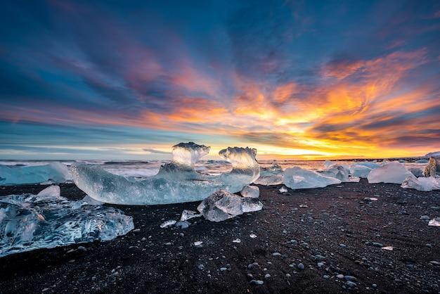 Praia de areia preta diamante ao pôr do sol na islândia