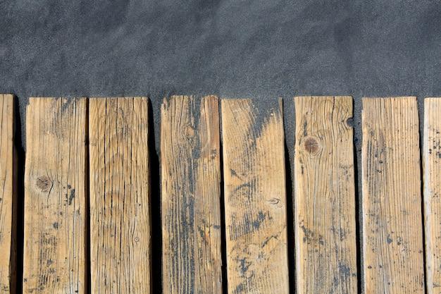 Praia de areia preta e piso de madeira