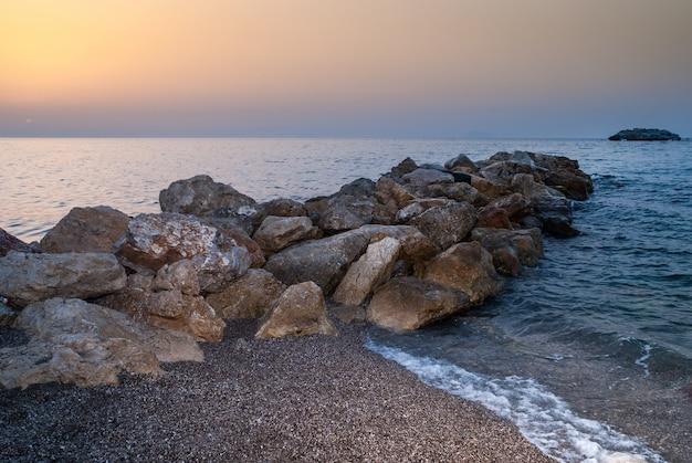 Praia de brolo ao pôr do sol. sicília