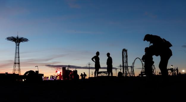 Praia de coney island em nova york. silhuetas de pessoas e torre de salto de pára-quedas em um fundo do sol